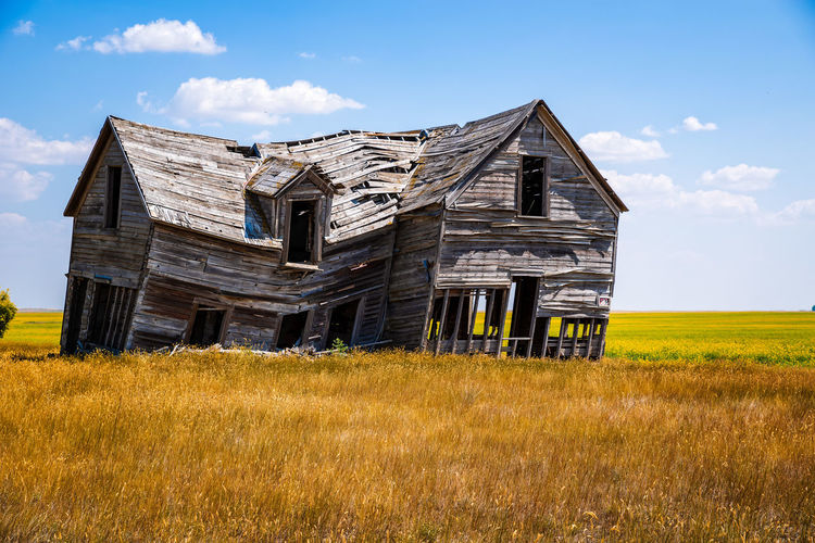 Abandoned building on field against sky