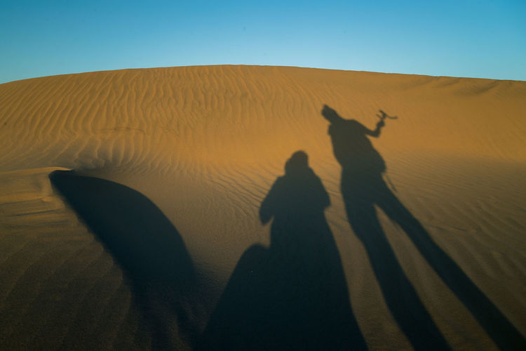 Shadow of people on sand dune