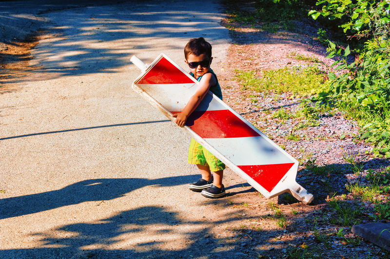 Little boy is carrying a construction site barrier across the street. To overcome difficulties Casual Clothing Child Childhood Day Full Length Holding Innocence Leisure Activity Looking At Camera Males  Men Nature One Person Outdoors Portrait Real People Shadow Shorts Sunlight