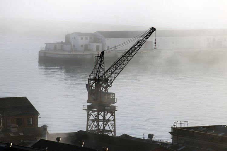 Crane by pier on sea against sky