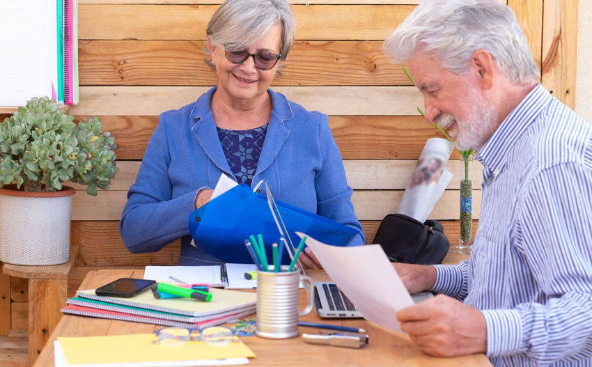 Senior man with woman holding document at table