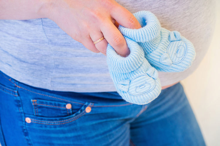 Pregnant woman holding blue baby booties, expecting boy Pregnant Woman Casual Clothing Childhood Close-up Human Body Part Human Hand Jeans Pregnancy Pregnancy Photography Pregnant Pregnant Belly  Pregnant Life Pregnant Phtography