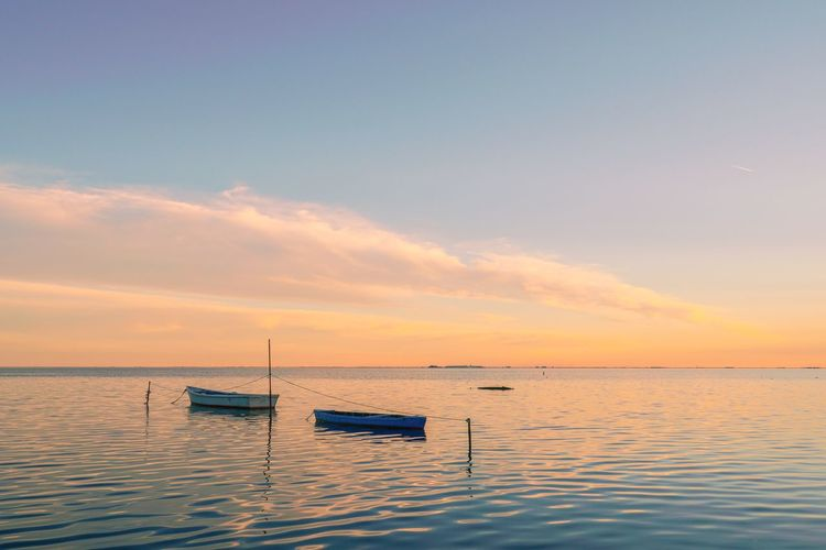 Sailboats in sea against sky during sunset
