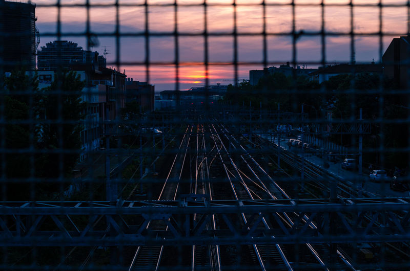 Railroad tracks seen through fence during sunset
