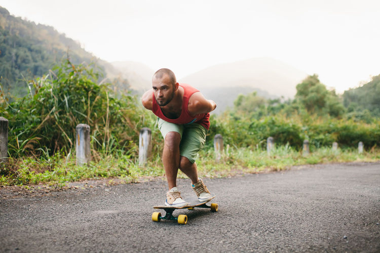 Man Skateboarding On Road Against Mountain