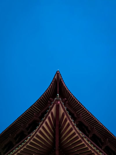 Low angle view of temple roof against clear blue sky