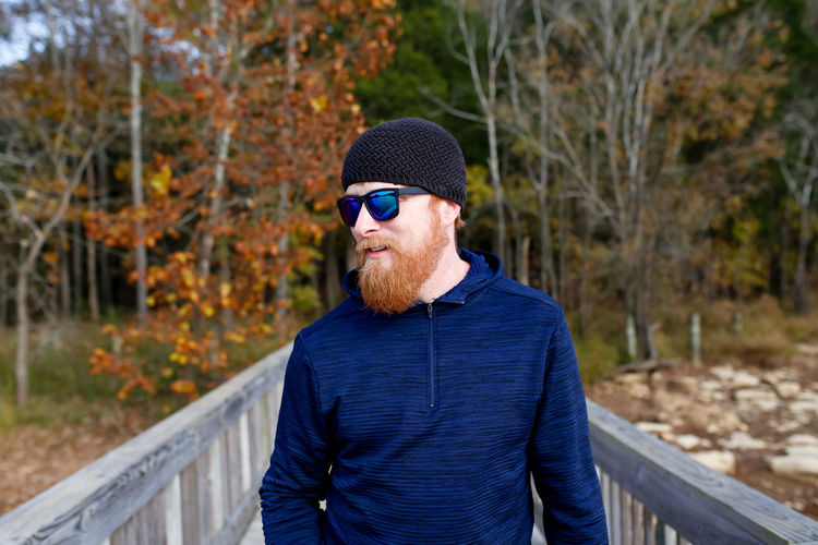 Redheaded man with beard standing by lake Red Head Beard Redhead Mammal Bearded Man Lake Nature Hike Nature Walk Sunglasses Facial Hair One Person Real People Focus On Foreground Tree Front View Day Casual Clothing Warm Clothing Outdoors Nature Fall Autumn Fall Colors Autumn colors Bridge