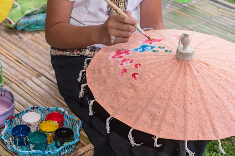 High angle view of woman hand holding multi colored umbrellas on table