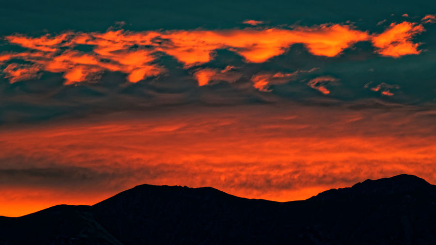 Beauty In Nature Cloud - Sky Dramatic Sky Environment Idyllic Landscape Mountain Mountain Peak Mountain Range Nature No People Non-urban Scene Orange Color Outdoors Remote Romantic Sky Scenics - Nature Silhouette Sky Sunset Tranquil Scene Tranquility