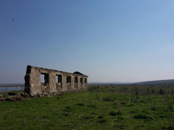 Old ruins on field against clear sky