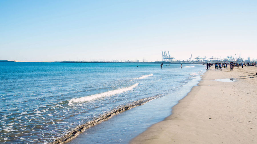 People on the beach of Valencia, Harbor cranes in the background Water Sky Sea Land Beach Clear Sky Copy Space Scenics - Nature Nature Sand Beauty In Nature Motion Day Incidental People Sport Wave Aquatic Sport Tranquility Tranquil Scene Outdoors