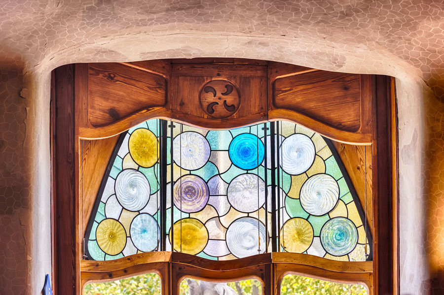 BARCELONA - AUGUST 9: Scenic ornate stained-glass window inside Casa Batllo, renowned building designed by Antoni Gaudi and iconic landmark in Barcelona, Catalonia, Spain, on August 9, 2017 No People Indoors  Wood - Material Architecture Built Structure Pattern Close-up Design Creativity Art And Craft Building Wall - Building Feature Arch Ceiling History Day Geometric Shape Shape Window Architectural Column Ornate Floral Pattern