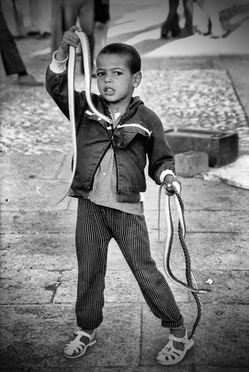 Moroccan boy with two cobra snakes - Tangier, Morocco A Taste Of Morocco Snakes Cobra Boy Morocco 🇲🇦 Casual Clothing Childhood Day Elementary Age Front View Full Length Holding Leisure Activity Lifestyles One Person Outdoors People Real People Snake Boy Standing Young Adult Inner Power