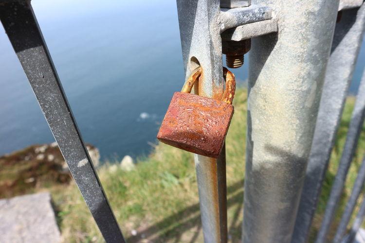 Close-up of rusty metal railing against sea