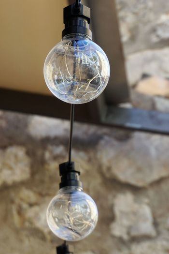Close-up of light bulb hanging against wall