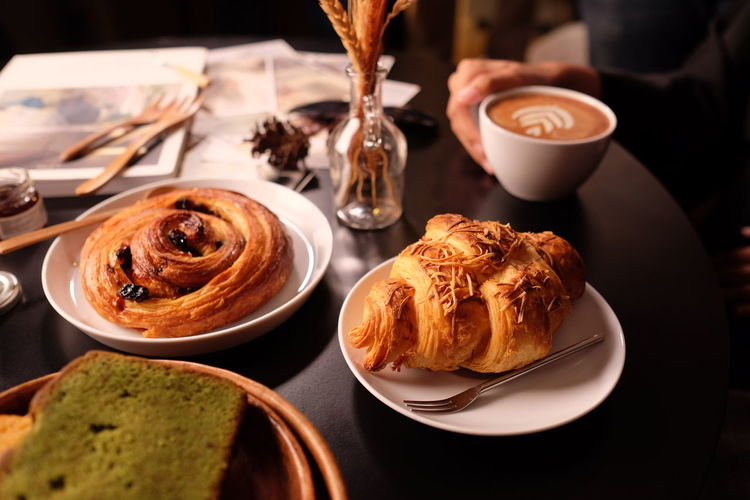 Close-up of coffee served and croissants on table