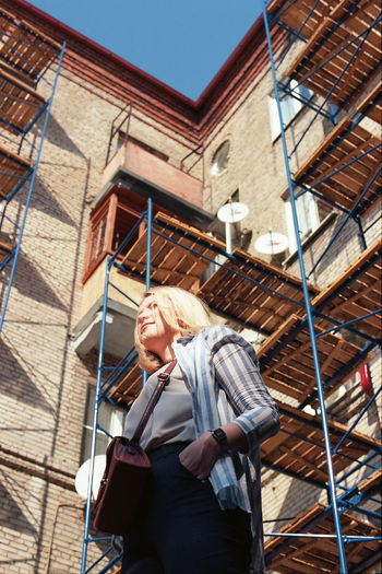Low angle view of woman standing against building