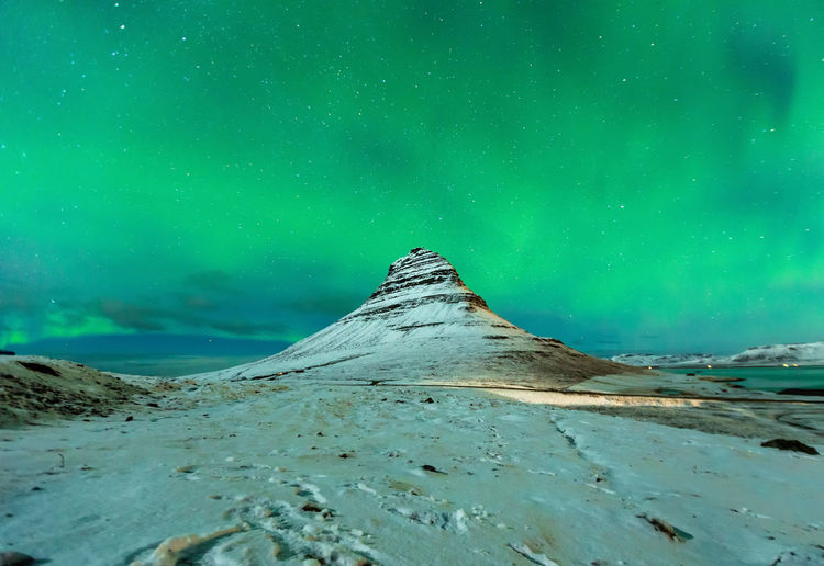 Aurora Borealis or northern light above kirkjufell mountain in iceland Aurora Borealis Iceland Kirkjufell Astronomy Beauty In Nature Cold Temperature Environment Green Color Idyllic Landscape Mountain Nature Night No People Non-urban Scene Scenics - Nature Sky Snow Snowcapped Mountain Star - Space Tranquil Scene Tranquility Water Winter