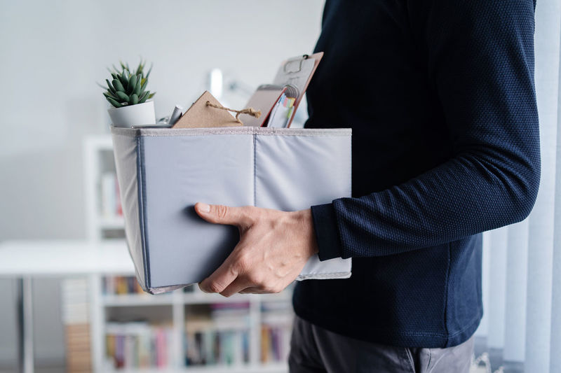 Midsection of man holding box in office