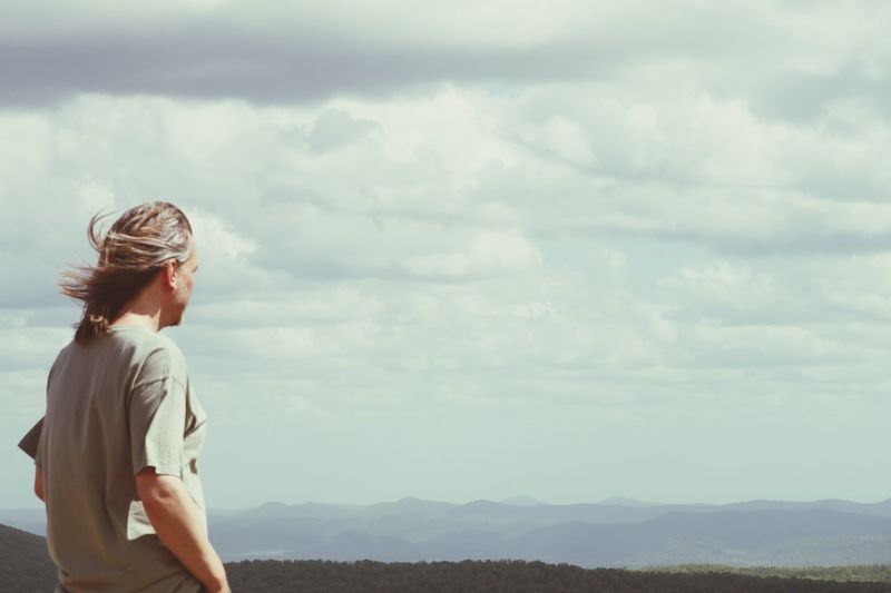 Man looking at view standing against cloudy sky