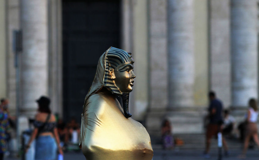 Street artist with sphinx mask in rome in piazza del popolo.