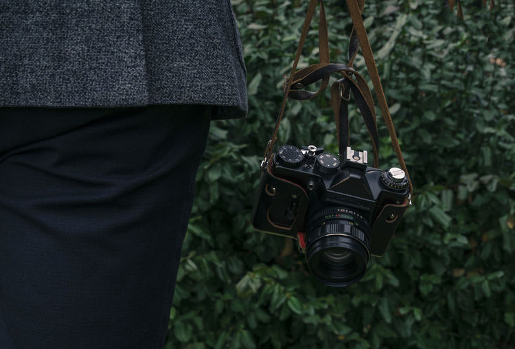Midsection Of Man With Camera Against Plants