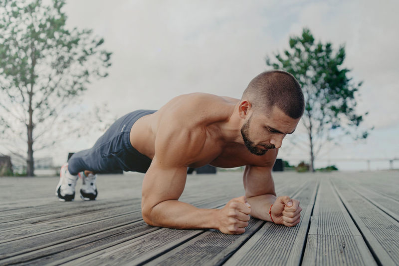 Shirtless young man exercising on footpath