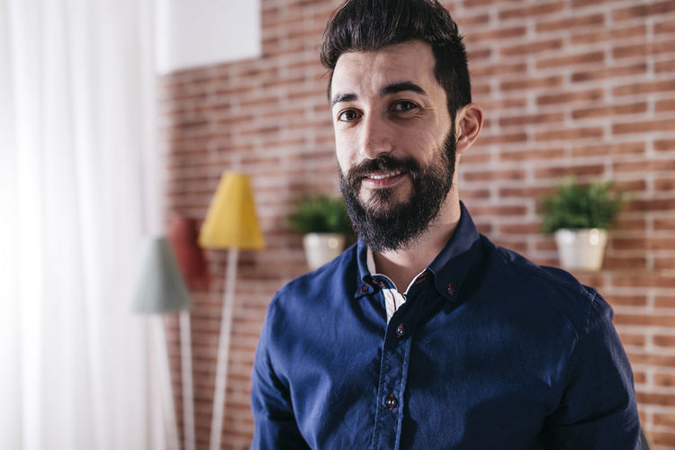 Portrait of mature man with beard wearing blue shirt smiling slightly at camera. Happy Adult Beard Domestic Life Home Interior Indoors  Lifestyles Looking At Camera Men Mid Adult Occupation One Person People Portrait Real People Smile Smiling Standing Working Young Adult