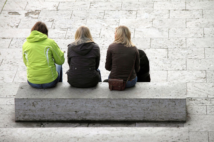 Rear view of three women sitting outdoors