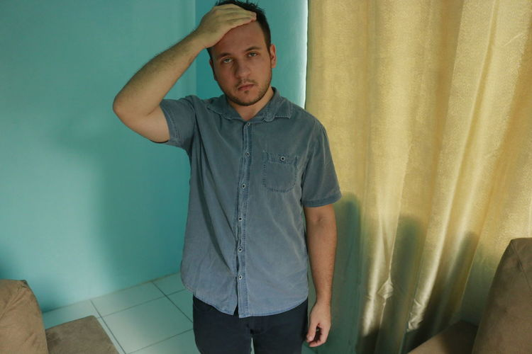 Blue Eyes One Person Indoors  Front View Curtain Standing Casual Clothing Young Adult Real People Young Men Men Lifestyles Three Quarter Length Looking Blue Home Interior Wall - Building Feature Looking Away Males  Contemplation