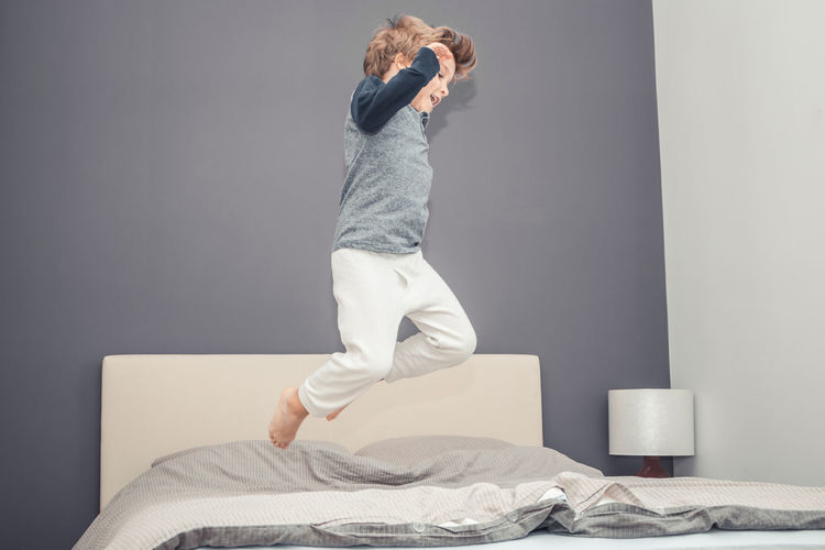 Full length of man jumping on bed at home