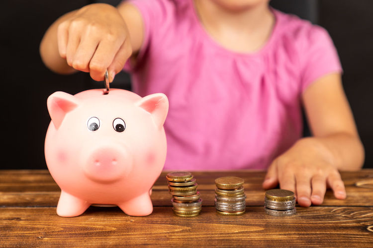 Midsection of girl inserting coin in piggy bank on table