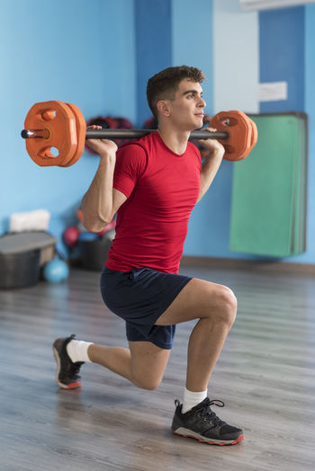 Man doing lunges with barbell at gym