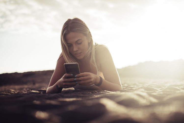 Young woman using smart phone at beach against sky