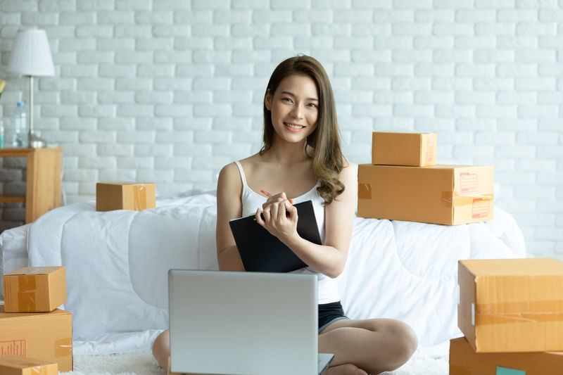 Portrait of woman using laptop while sitting amidst cardboard boxes at home