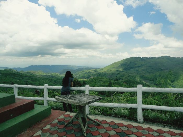 Man looking at view mountains against cloudy sky