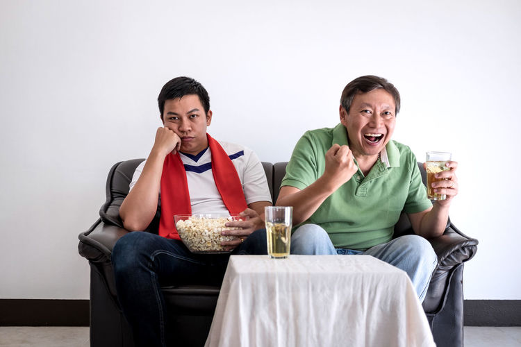 Family With Food And Drink Watching Sports On Tv At Home