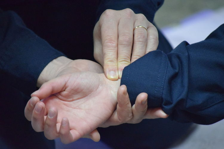 Midsection of man holding hand of woman