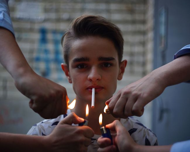 Hands igniting cigarette of teenage boy