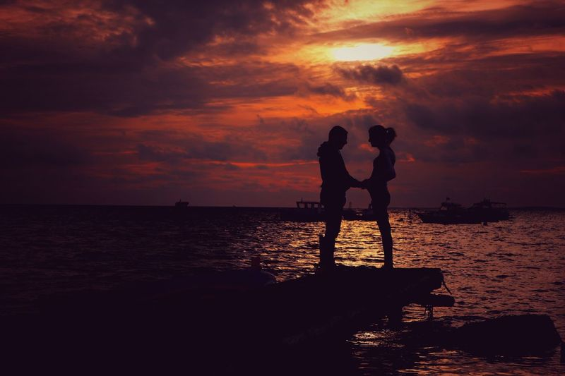 Silhouette couple standing at beach against cloudy sky during sunset