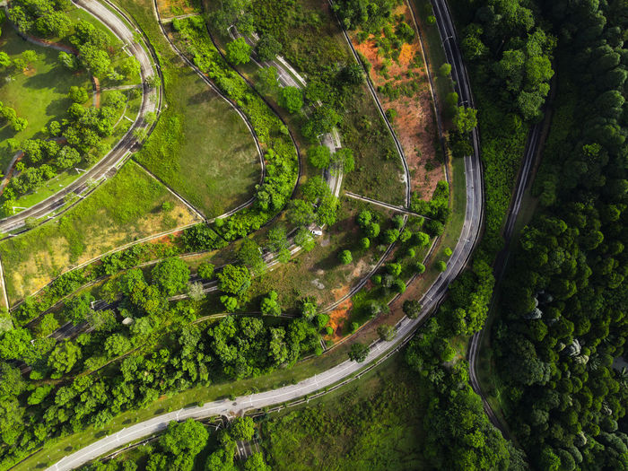 Aerial view of nature abstract with winding road and pond