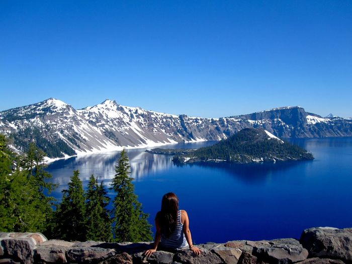 Woman sitting at lakeshore against snowcapped mountains