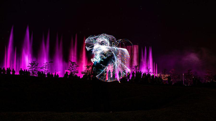 Illuminated firework display at night