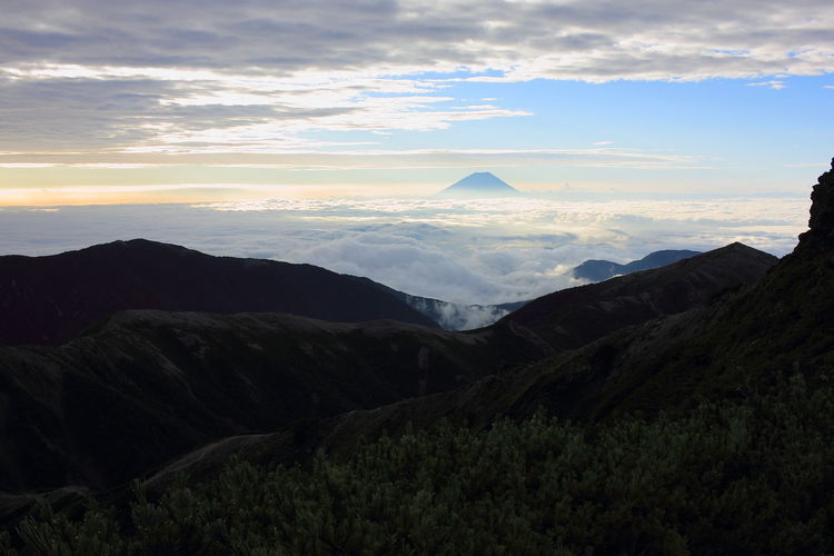 Mid Distance View Of Mt Fuji Against Cloudy Sky