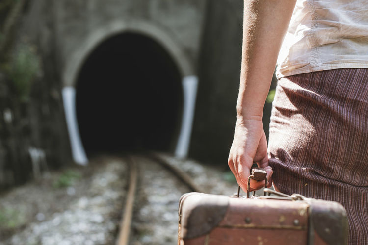 Midsection of woman holding suitcase while standing on railroad track
