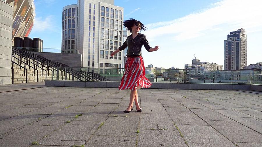 Full length of woman standing on city against sky