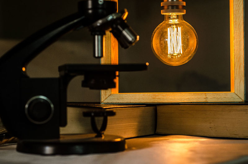 Microscope against illuminated light bulb picture frame in darkroom