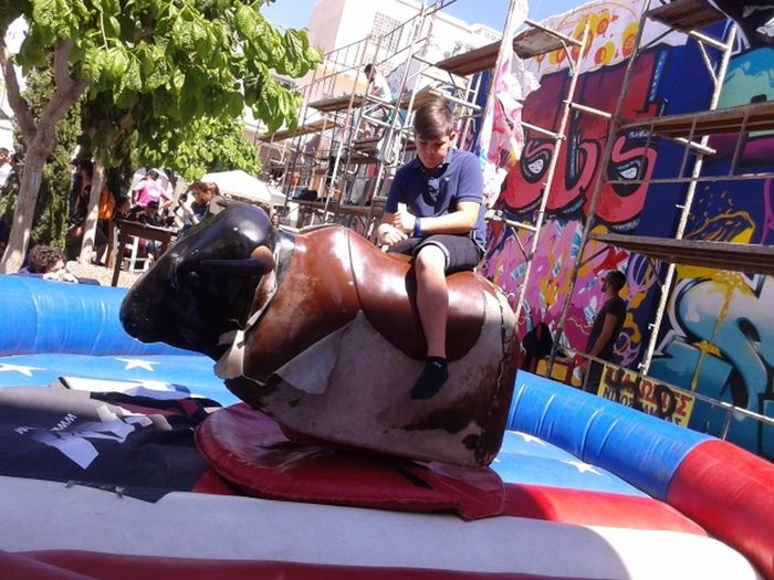 Art Blue Bucking Bronco Casual Clothing Day Graffiti Festival Leisure Activity Lifestyles Mechanical Bull  Mechanical Bull Boys Mechanical Bull Kids Multi Colored Outdoors Street Festival Cy Street Festival Mechanical Bull