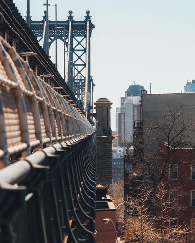 Manhattan bridge in city against sky