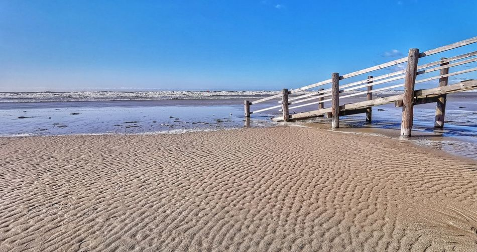 Sea And Sky Beach Photography Beach Day Wood Wood - Material Wooden Bridge No People Non-urban Scene Sky And Clouds Waterfront Water Reflections Blue Sky And Clouds Blue Sky Water Clear Sky Sea Beach Sand Blue Sunny Sky Horizon Over Water Low Tide Tide Seascape Bay Of Water Coastline Ocean Wave Coast